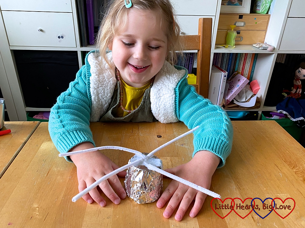 Sophie sticking two pipe cleaners to the foil-covered bottom half of the polystyrene cup