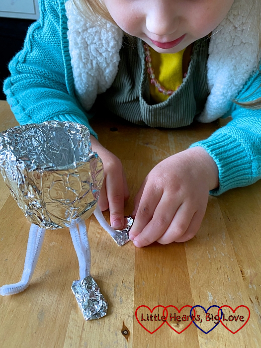 Sophie bending the pipe cleaners and wrapping a small piece of foil around the bottom of each