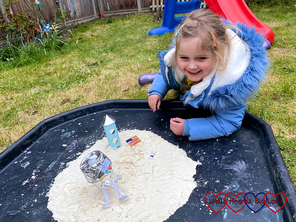 Sophie playing with the lunar module, toilet roll tube rocket and astronaut in the moon sand in the tuff tray