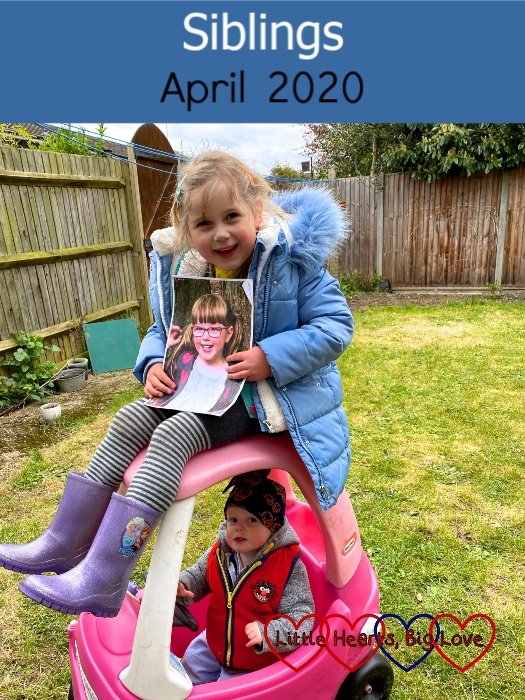 "Sophie holding a photo of Jessica and sitting on top of the Little Tikes car with Thomas sitting inside it - ""Siblings - April 2020"""
