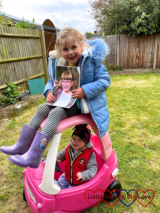Sophie holding a photo of Jessica and sitting on top of the Little Tikes car with Thomas sitting inside it