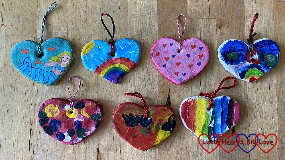 Seven colourful salt dough hearts painted with various designs