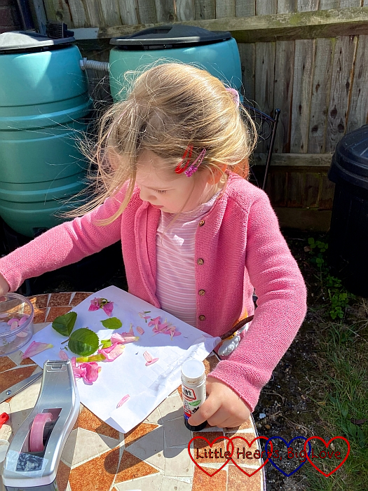 Sophie sticking leaves and petals to a piece of paper to create her nature art picture.