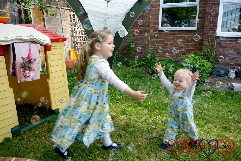 Sophie and Thomas playing with bubbles in the garden with a picture of Jessica hanging in the doorway of the playhouse
