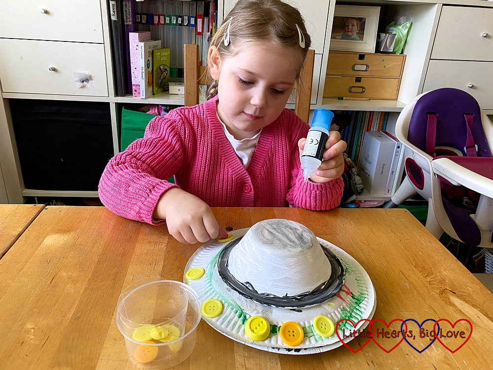 Sophie glueing yellow buttons on to her paper plate flyer saucer