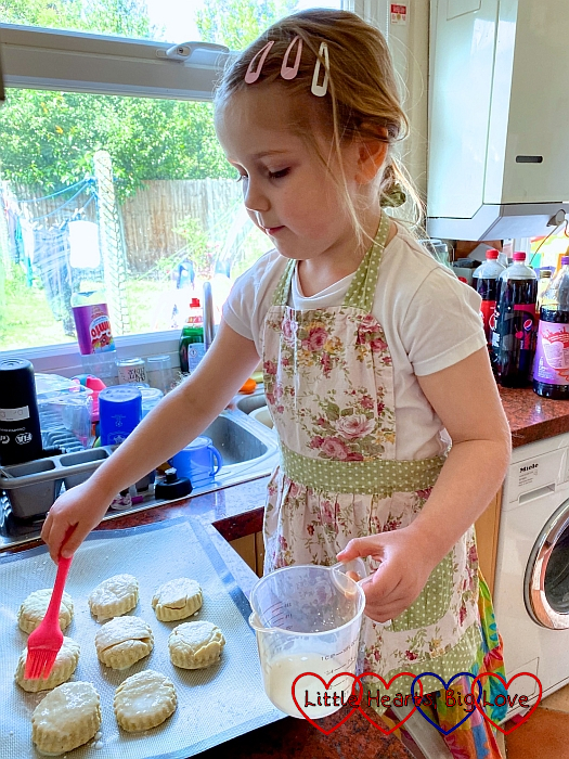 Sophie brushing milk on scones before they go in the oven