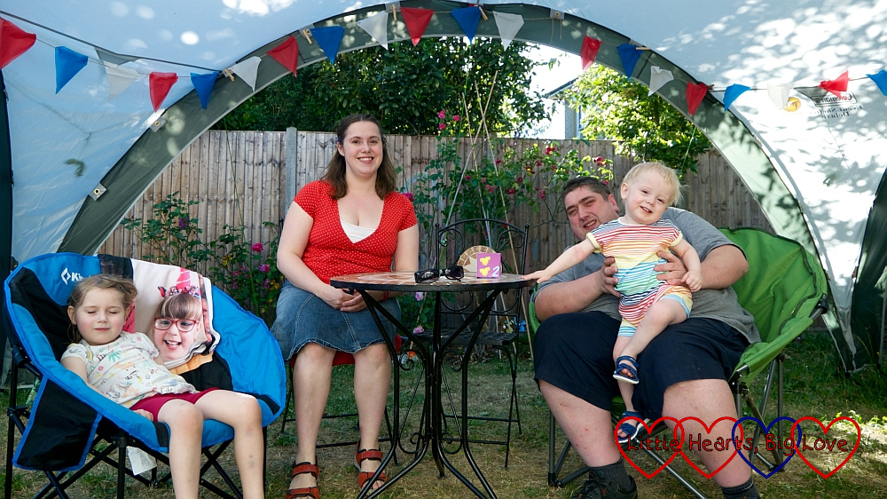 "Sophie, me and hubby (holding Thomas) sitting on garden chairs in the ""party tent"" with Jessica's photo draped over Sophie's chair"