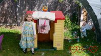 Sophie and Thomas standing by their playhouse, with Jessica's photo blanket hanging down from the roof and bubbles coming from the bubble machine on top of it