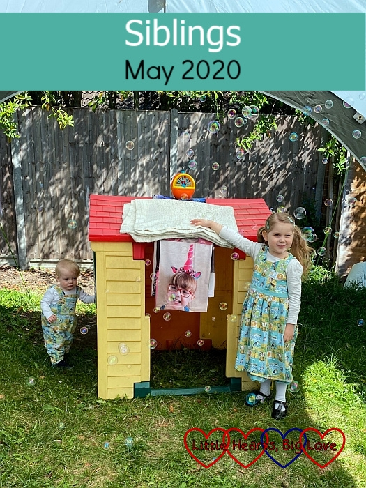 "Sophie and Thomas standing by their playhouse, with Jessica's photo blanket hanging down from the roof and bubbles coming from the bubble machine on top of it - ""Siblings - May 2020"""