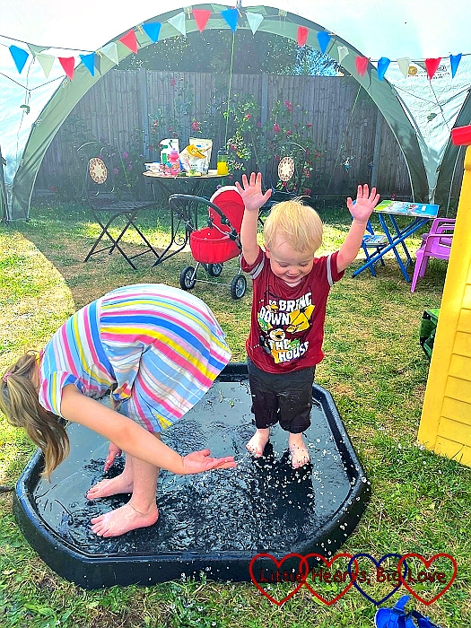 Sophie and Thomas splashing in a tuff tray filled with water