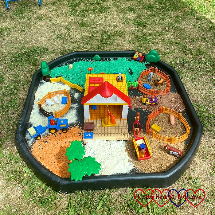 A farm scene set up in the tuff tray with coloured rice and various cereals used to create different areas