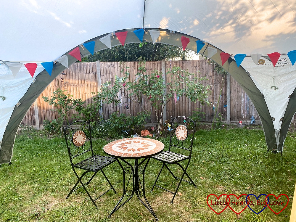 """Two chairs and a table inside our """"party tent"""" with red, white and blue bunting above them"""