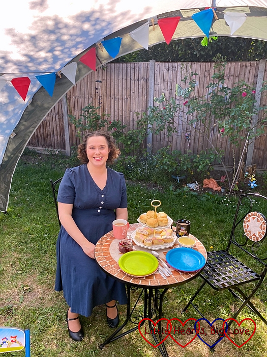 Me wearing a 1940s-style dress sitting out in the garden with a cake stand on the table next to me and blue, white and red bunting above me