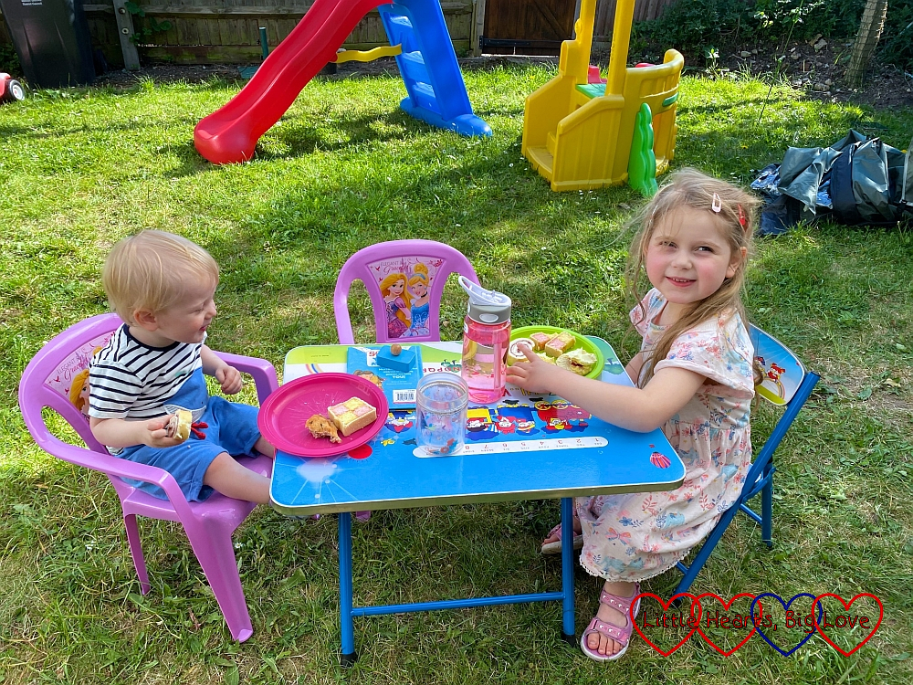 Thomas and Sophie sitting at their little table in the garden enjoying some cake