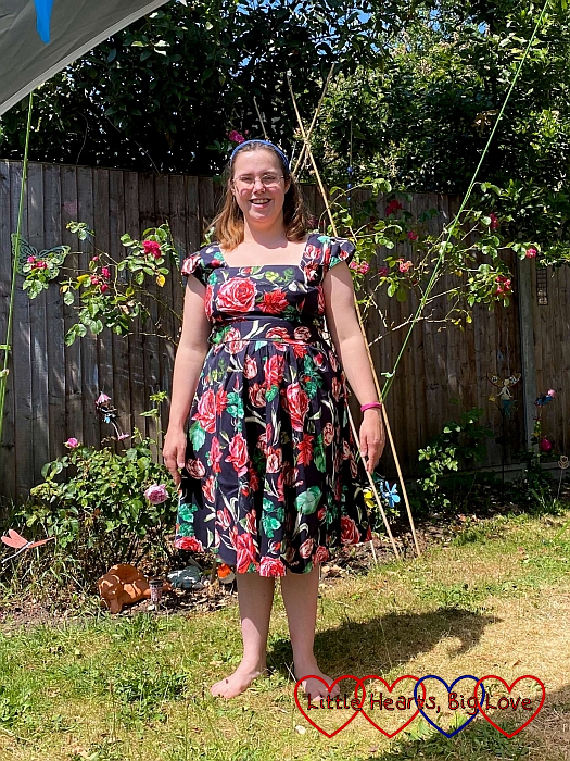 Me wearing a 50s style dress made of black fabric with red flowers printed on it