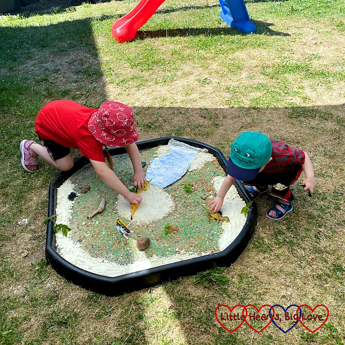 Sophie and Thomas playing in the tuff tray which is set up for dinosaur small world play