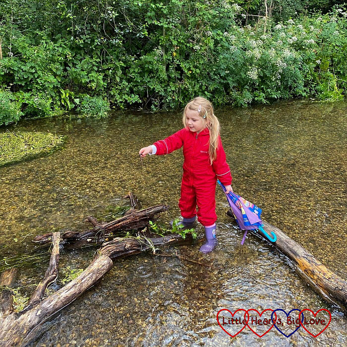 Sophie in her red puddle suit standing in the river at Denham Country Park
