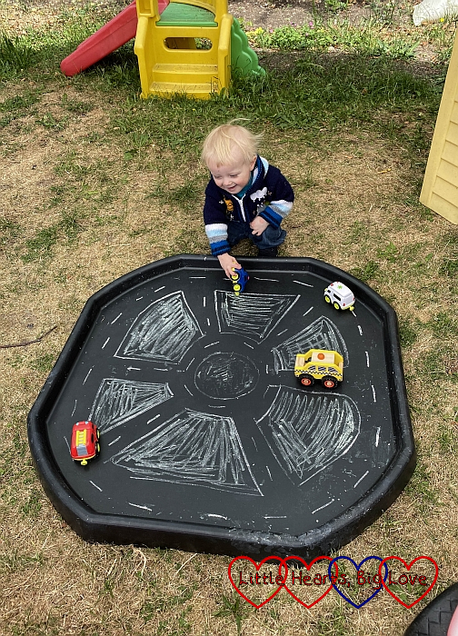 Thomas playing with the cars inside the tuff tray which is marked out with roads in chalk