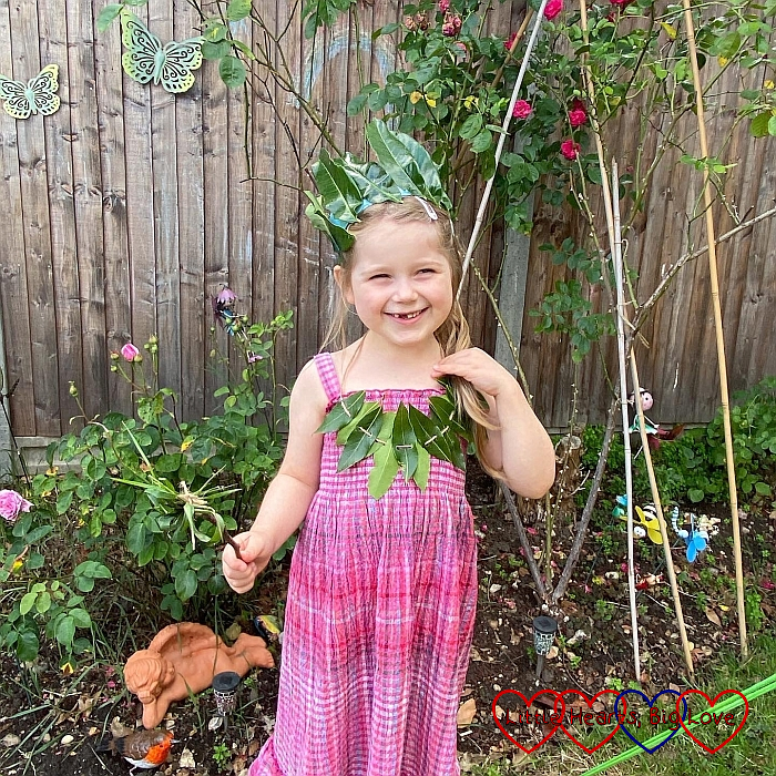 Sophie wearing a leaf necklace and a leaf crown, holding a grass wand