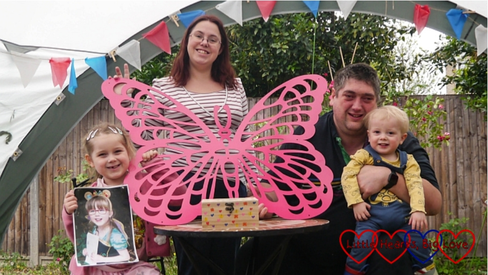 Sophie (holding a photo of Jessica), me (holding Jessica's memorial butterfly with her memory box on the table in front of it) and hubby holding Thomas, out in the garden