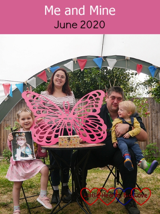 "Sophie (holding a photo of Jessica), me (holding Jessica's memorial butterfly with her memory box on the table in front of it) and hubby (holding Thomas who is looking at him), out in the garden - ""Me and Mine: June 2020"""