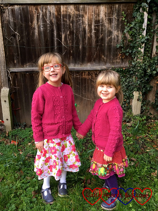 Jessica and Sophie holding hands and wearing matching cardigans. Jessica is wearing her flowery skirt and Sophie has an elephant print skirt