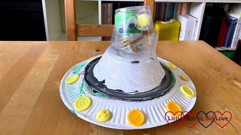 The finished flying saucer with an alien inside the capsule