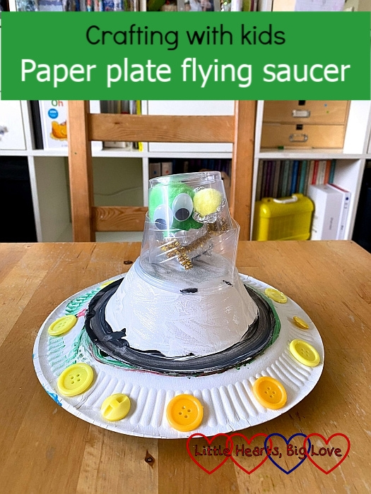 "A paper plate flying saucer with a pompom alien inside the capsule on the top - ""Crafting with kids: Paper plate flying saucer"""