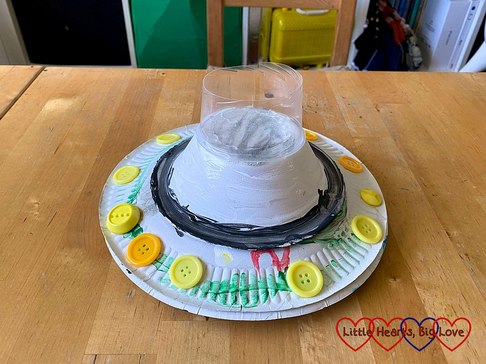 The paper plate flying saucer with half a plastic cup stuck to the top of the paper bowl