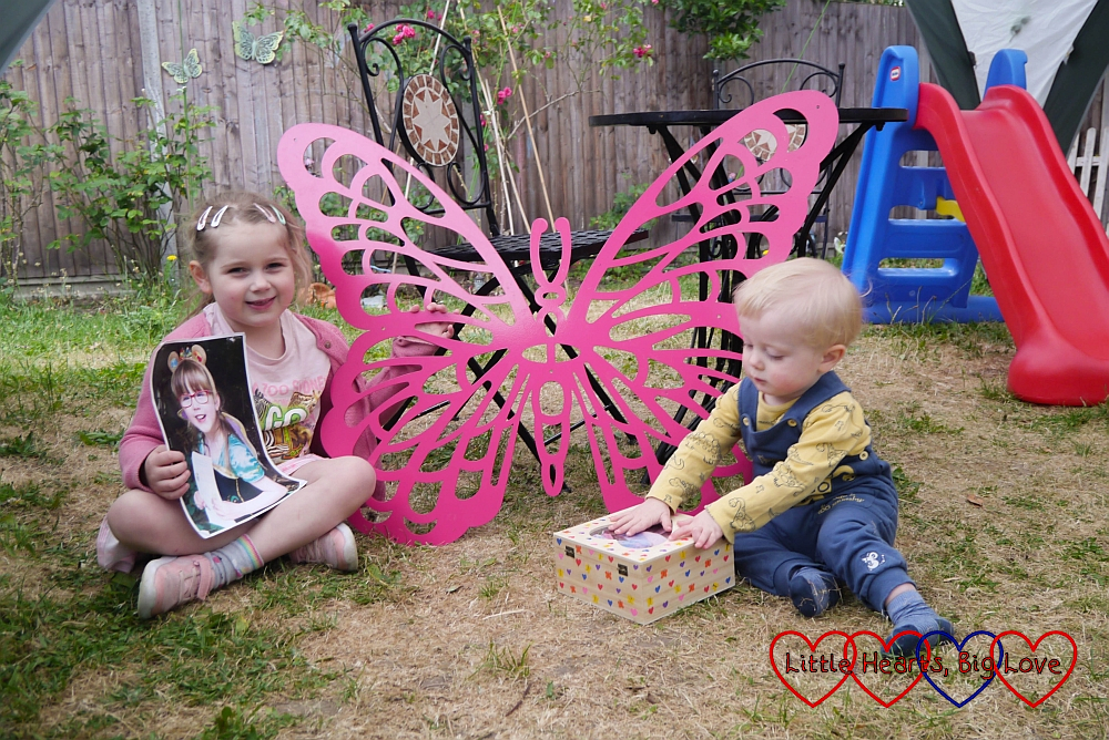 Sophie (holding a picture of Jessica) and Thomas in front of Jessica's memorial butterfly