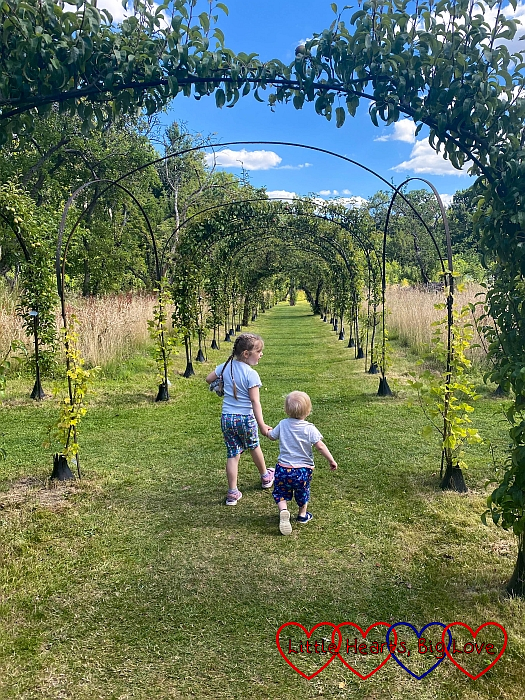 Sophie and Thomas walking through the Round Fruit Garden at Cliveden