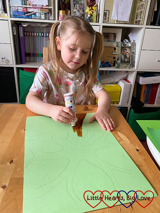 Sophie colouring in the outline of a tree on green cardboard