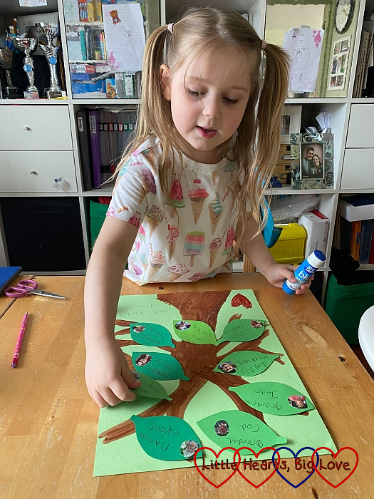 Sophie sticking her green cardboard leaves to the family tree picture