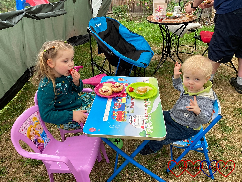 Sophie and Thomas sitting at their table in the garden eating cakes