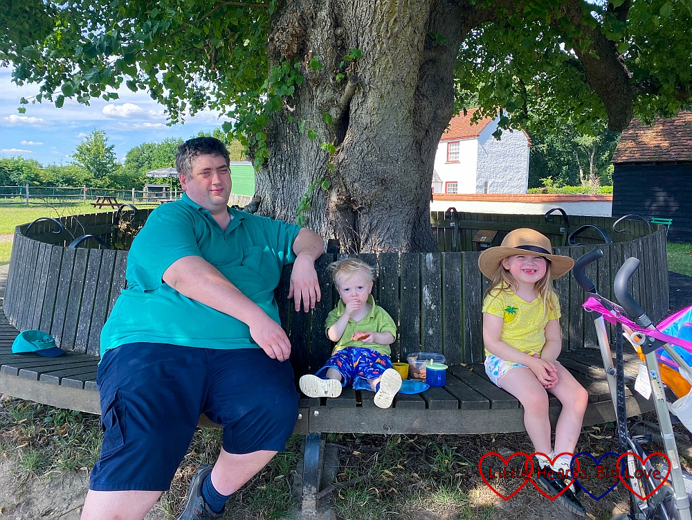 Hubby, Thomas and Sophie sitting on a bench in front of a tree at Chiltern Open Air Museum