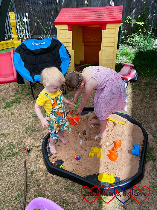 Sophie and Thomas playing in the sand tray in the garden