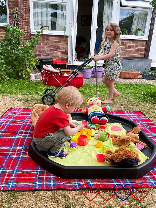 Thomas playing with the tea set and toys in the tuff tray while Sophie pushes her doll's pram around the garden