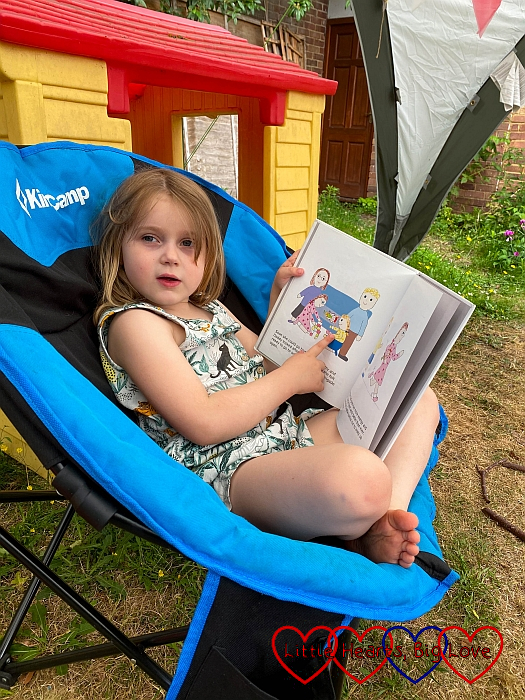 Sophie sitting in a garden chair with the 'Jessica has a heart operation' book
