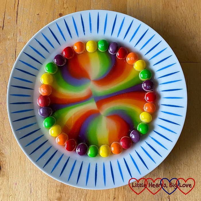 Skittles around the edge of a plate with rainbow patterns in the middle of the plate