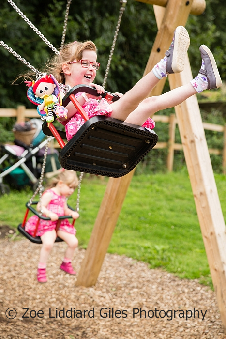 A very smiley Jessica on a swing with her Kerry doll