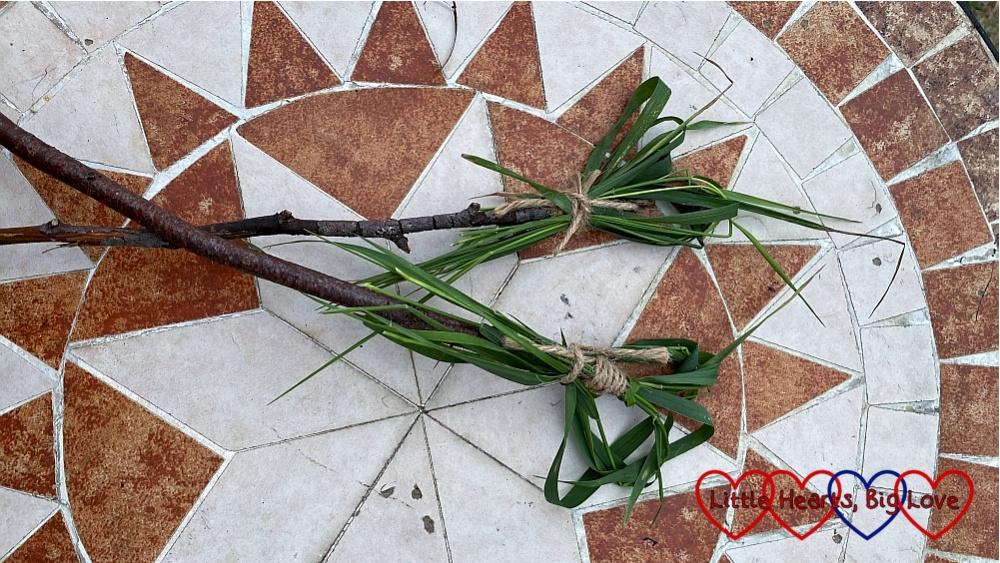 Two wands made from sticks with grass tied at the top in a heart shape