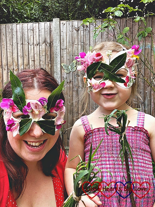 Me and Sophie wearing cardboard masks decorated with leaves and petals