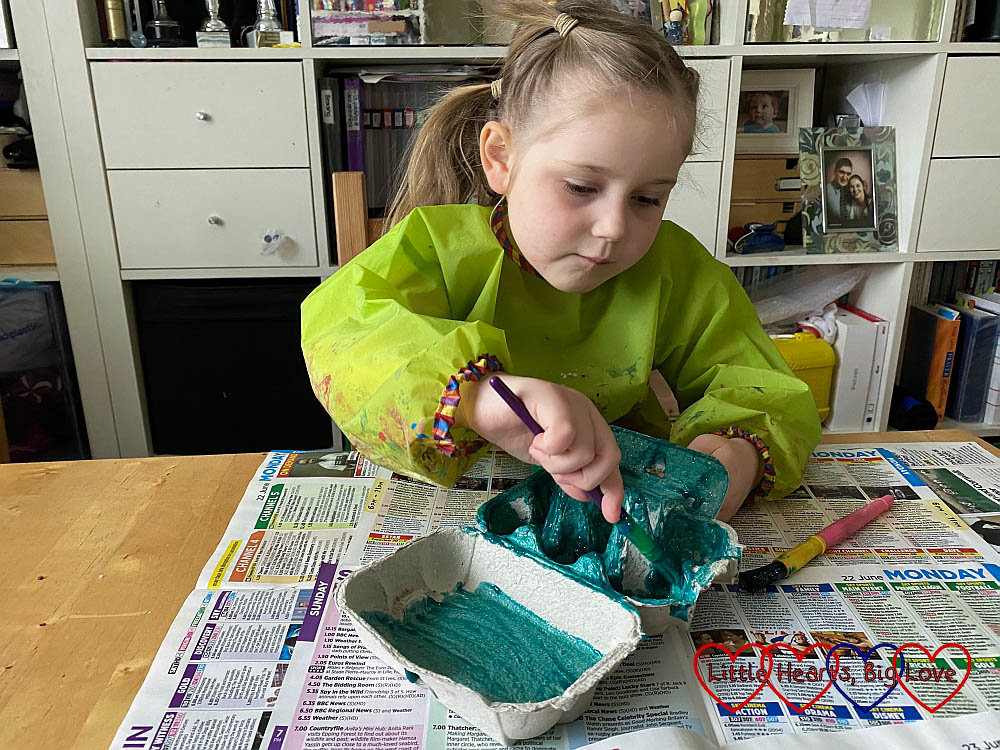 Sophie painting the inside of her egg box with green-blue paint