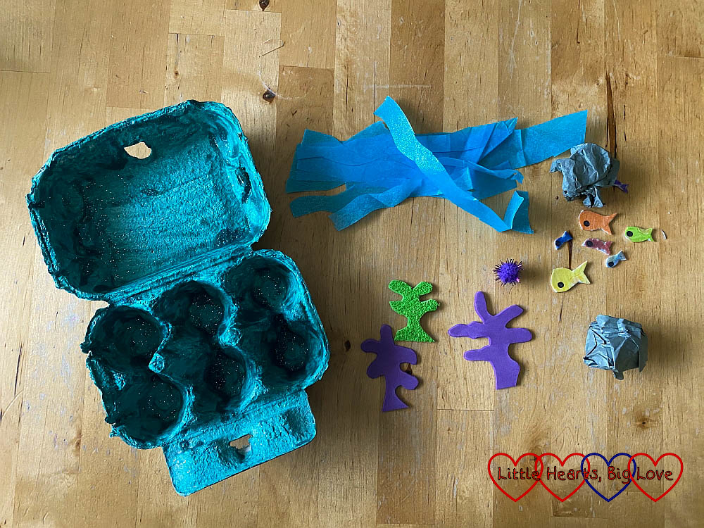 A green-blue painted egg box with blue tissue paper strips, grey tissue paper scrunched into balls and seaweed and fish shapes cut out of craft foam