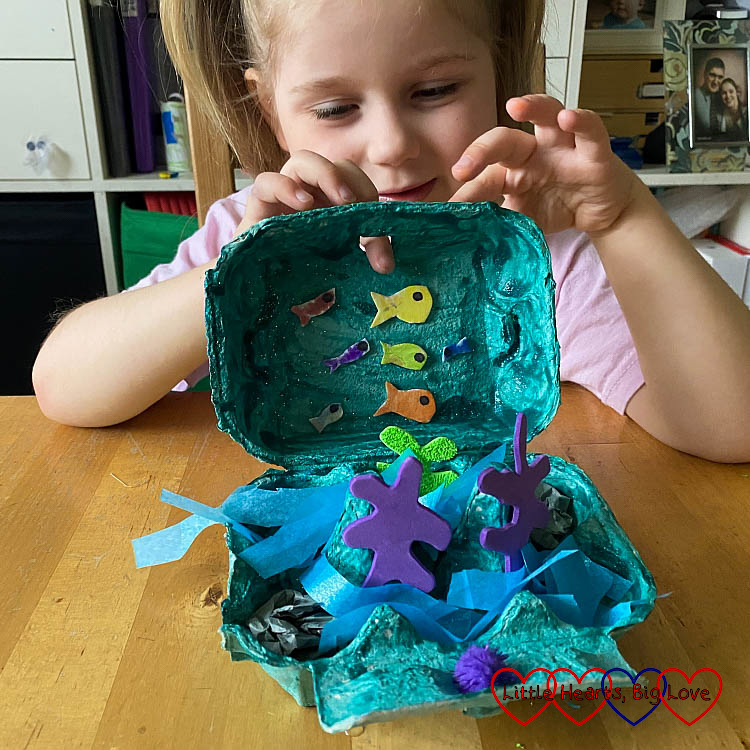 Sophie with her finished ocean in an egg box