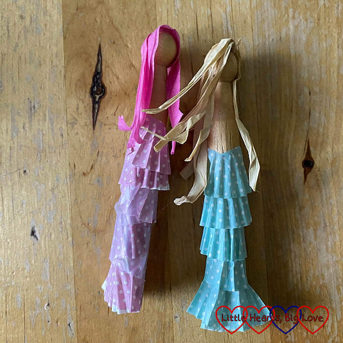 Two dolly pegs - one with pink petits-fours cases around the bottom and pink raffia stuck on for hair; the other with blue petits-fours cases and beige raffia