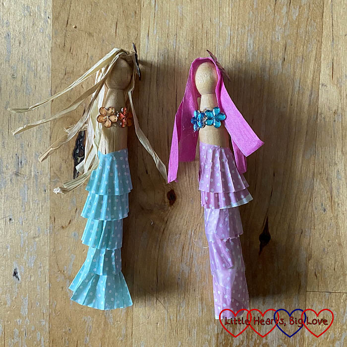 Two mermaid peg dolls - one with a tail made from pink petits-fours cases, pink raffia hair and blue gems for a bikini top; the other with blue petits-fours cases, beige raffia and pink gems