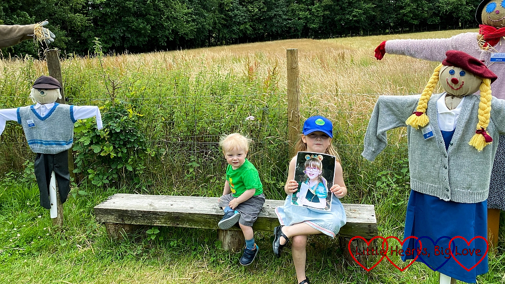 Sophie (holding a photo of Jessica) and Thomas sitting on a bench in between a family of scarecrows