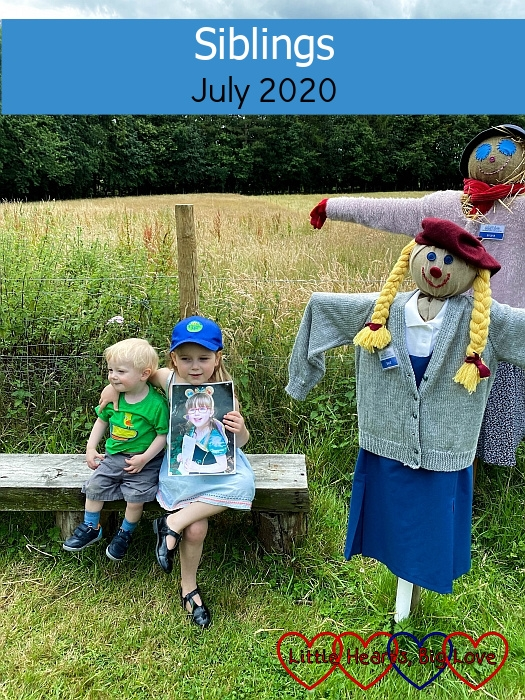 "Sophie (holding a photo of Jessica) and Thomas sitting on a bench in between a family of scarecrows - ""Siblings - July 2020"""