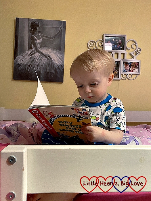 Thomas sitting on Sophie's bed looking at a book